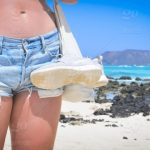 Girl wearing denim shorts with a naked belly on the beach during summer,  with space for copy stock photo 5a2dbcae-1a44-4dae-8549-9d30808c5ce6