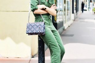 An army green jumpsuit is worn with a chain shoulder bag, white pumps, and  mirrored sunglasses