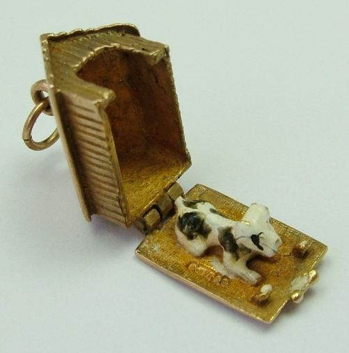 A 1960s English 9ct gold charm of a kennel that opens to reveal an enamel painte…
