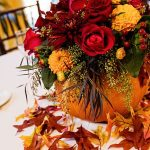 Add a hint of Halloween to your wedding reception with pumpkin floral centerpiec...