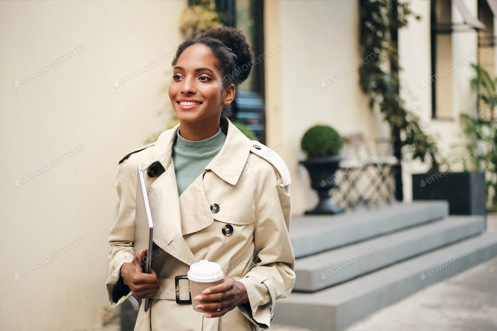 African American business woman in stylish trench coat confidently walking down …