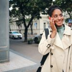 Beautiful African American girl in stylish trench coat happily talking on cellph...