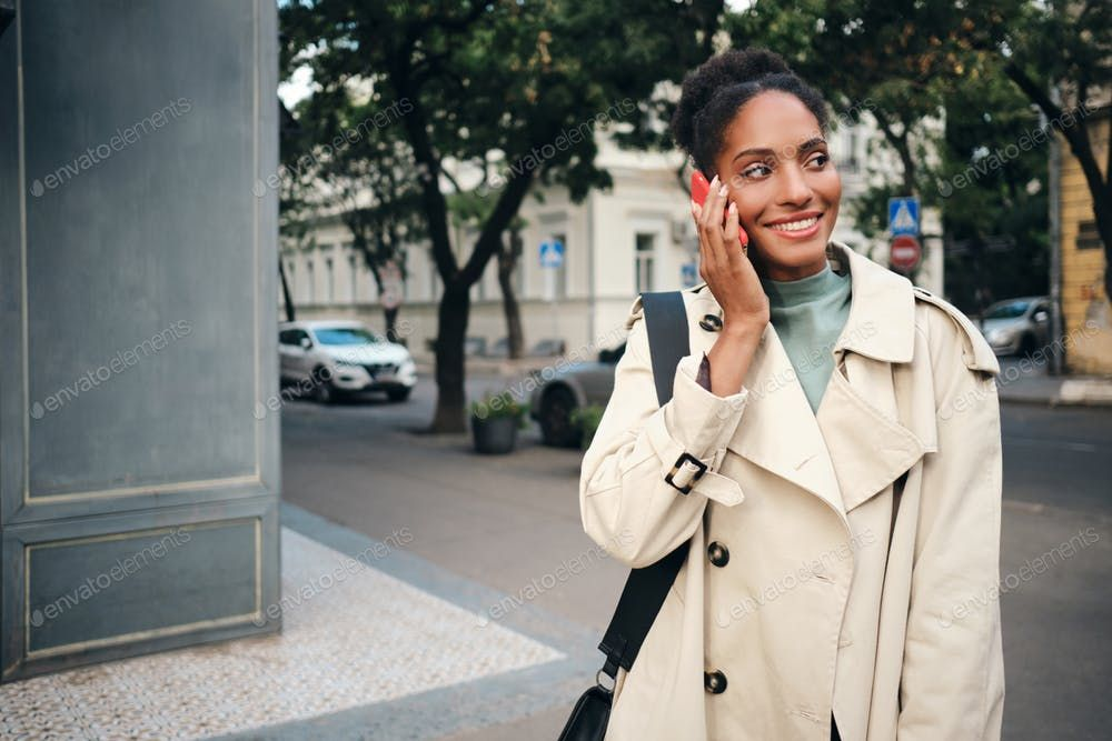 Beautiful African American girl in stylish trench coat happily talking on cellph…