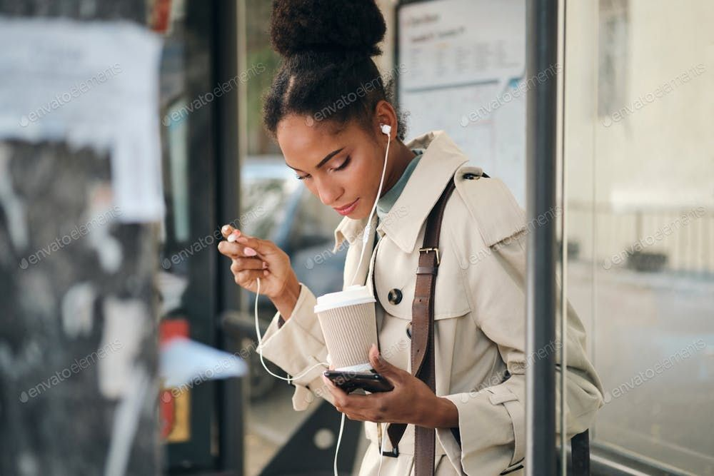 Beautiful African American girl in stylish trench coat with coffee and cellphone…