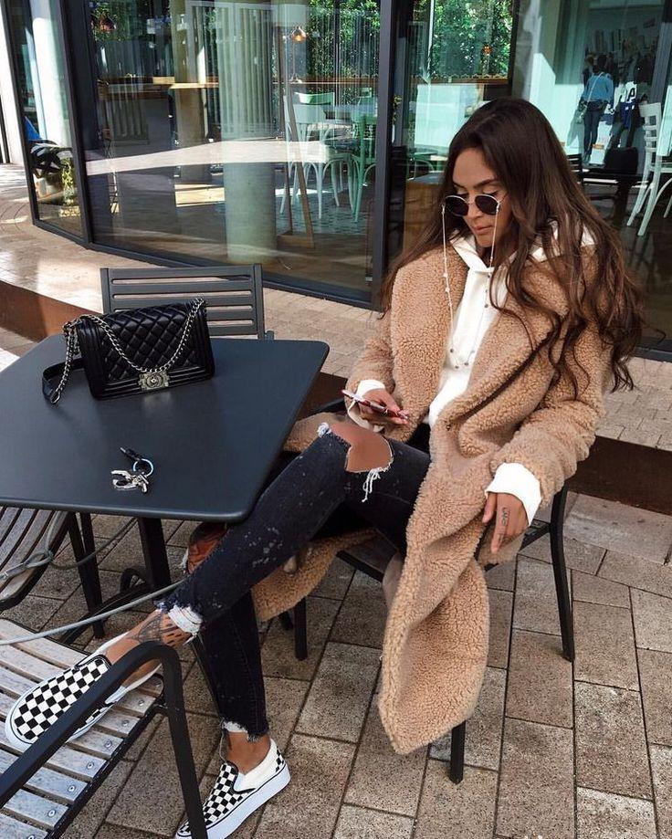 Mode Frau Herbst / Winter mit einem Plüschmantel, einem beigen Sweatshirt, Jeans