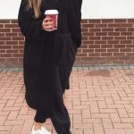 Modebewusste Frau hält sich bequem lässig mit einem schwarzen Jog einem lang B...
