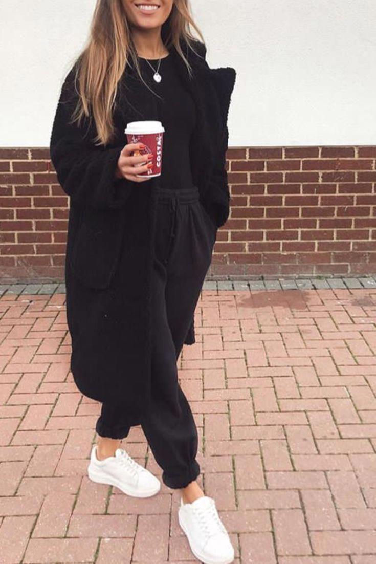 Modebewusste Frau hält sich bequem lässig mit einem schwarzen Jog einem lang B…