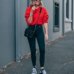 Picture Of a red jumper, black high waist skinnies, black sneakers and a small b...