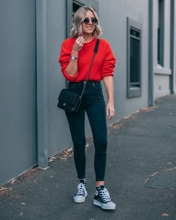 Picture Of a red jumper, black high waist skinnies, black sneakers and a small b…