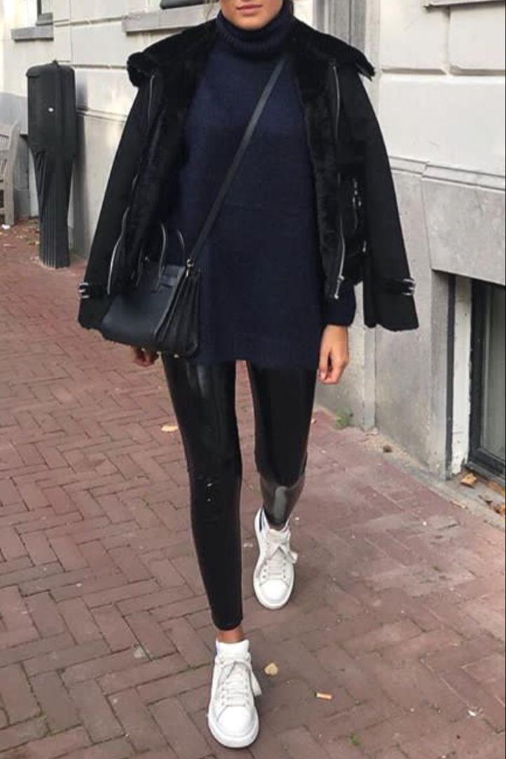 Trendy fall / winter fashion women with leatherette pants, white sneakers and …